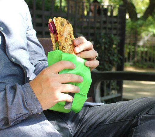 Chico con porta bocadillos verde en un parque
