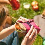 Chica con porta bocadillos rosa en picnic rolleat