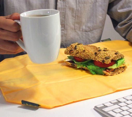chico desayunando con porta bocadillos amarillo en la oficina